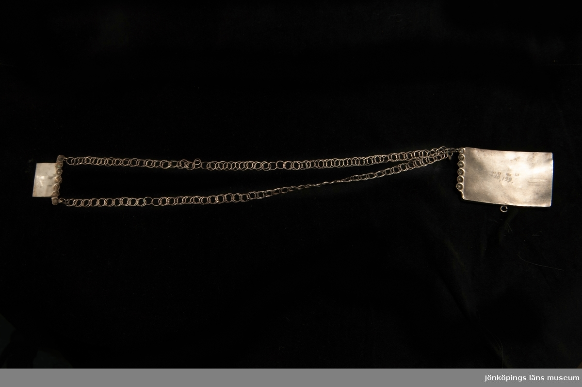 Ett halslås av silver med två enkla kedjor. Fronten prydd med filigranarbete med infattade,slipade glasstenar i rött och grönt. Undertill liten krok för hjärtformat hänge el. dyl.