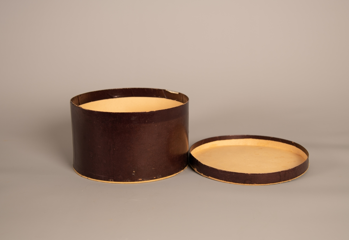 Rund hatteeske med lokk. Esken er laget av papp. Ikke noe mønster på pappen inne i esken. Festet på en lapp med håndskrift utenpå esken, som er vanskelig å tyde. (Se bilde). Spor av hattehår i esken.