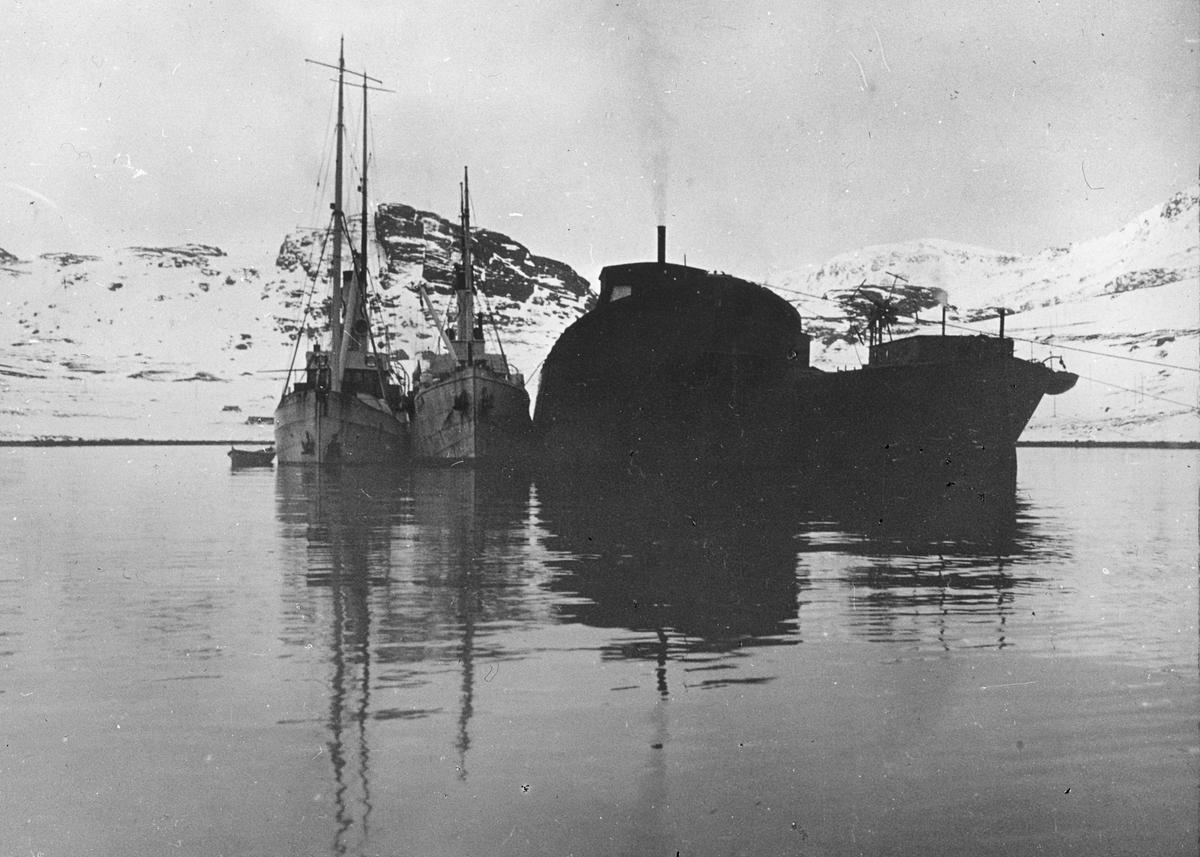 To dampskip og en robåt ligger ved siden av to opphugningsskip i en snødekket fjord.