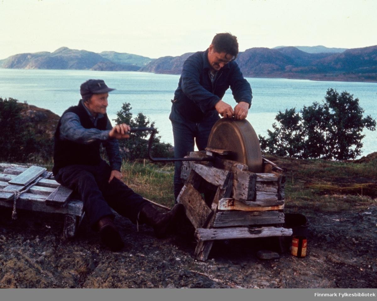 """Kunes, sommeren 1964. I bukta på vestsiden av utløpet til Storelva. Per Ole Andersen Matus (Varanger-Ola) drar slipesteinen, mens Edvard Johansen sliper kniven. Per Ole Andersen Matus er registrert født i 1891 i Nesseby. Foreldre er Anders Henriksen Matus, født 1834 i Enare Finland og Bigga Persdatter, født 1862 i Nesseby. De er registrerte i 1900 som fiskere og gårdbrukere. Kunes (samisk: Gussanjárga) er en bygd i Lebesby kommune i Finnmark. Stedet ligger innerst i Storfjorden. Fylkesvei 98 passerer igjennom Kunes. Fotografen, Richard Bergh, har også skrevet et hefte som heter: """"Når vi sitt' her og prate"""". Folk i Laksefjord forteller. Norsk Folkeminnelags skrifter nr. 122. H. Aschehoug & Co. (W. Nygaard). Oslo 1980. ISBN 82-03-10187-9"""