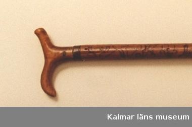 KLM 1648. Runstav. Nästan trind käpp av björk med tvågrenig krycka och doppsko av järn med mässingsring. Årtalet 1754 inskuret nära kryckan. Runor och figurer väl utarbetade.
