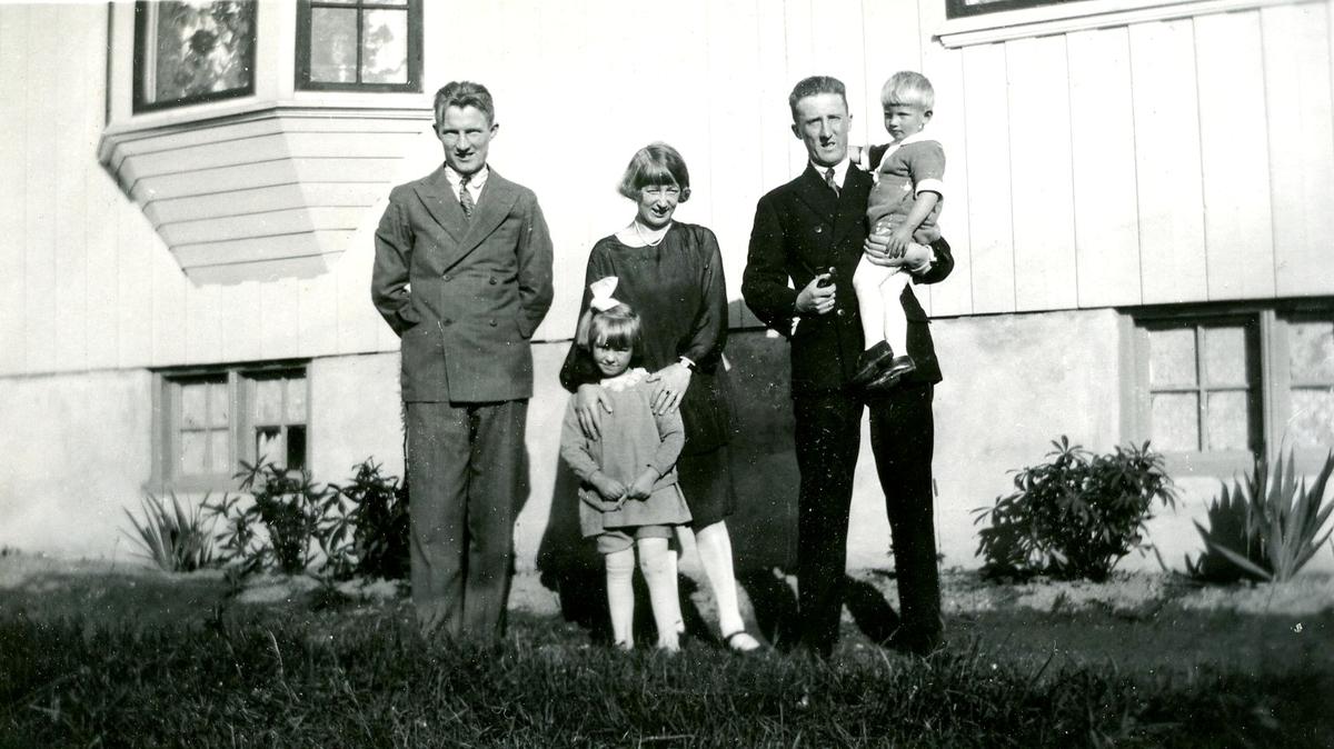 5 ukjende personar fotografert utanfor eit hus.