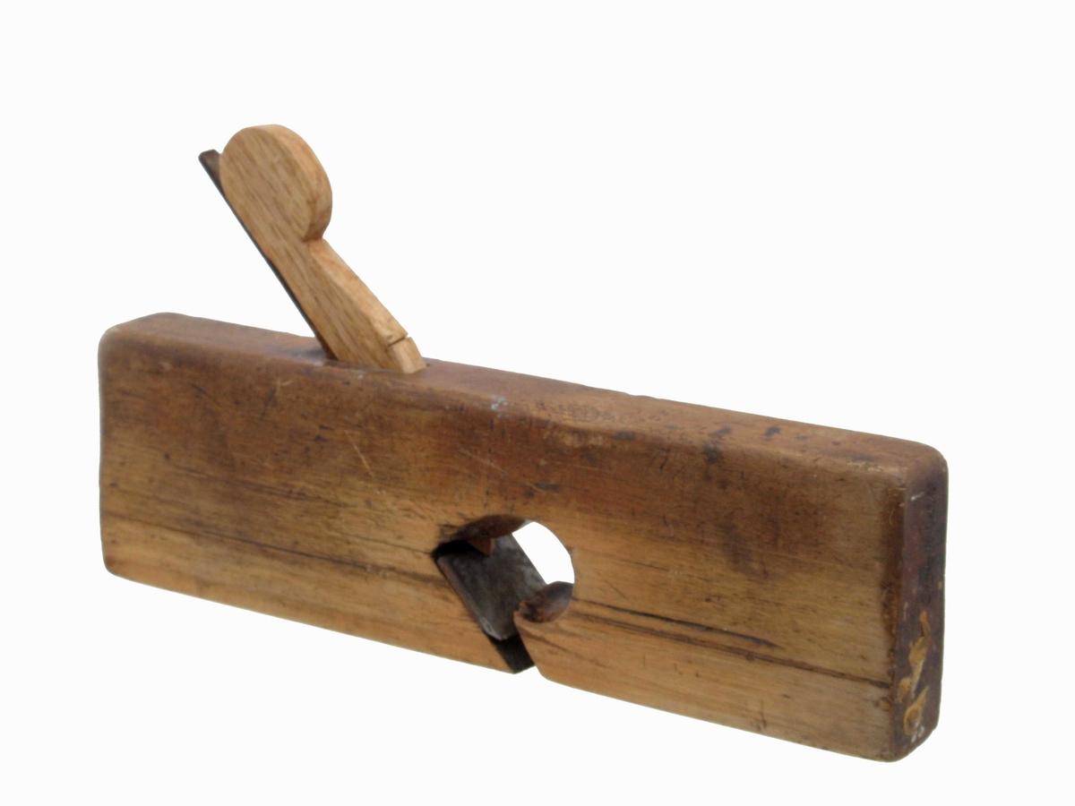 Høvel. Lyspolert tre med eikekile (ny). Flat såle med to små runde kvisthull. Jernet uten synlige stempler, er blankslipt.