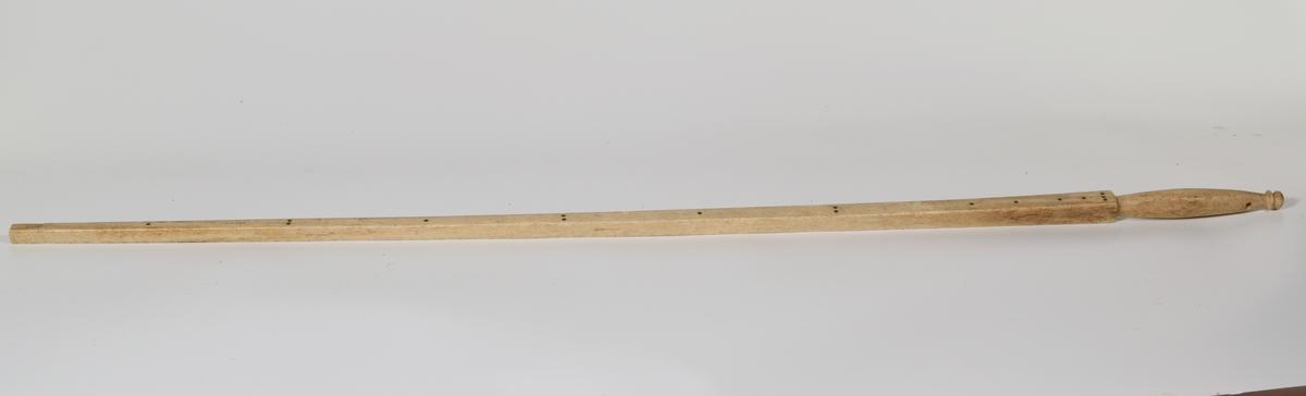 Kvadratisk tverrsnitt, utvides oppover, på 1 side innsatt flate nagler med mellomrom; håndtak balusterformet, profilert i enden; svakt buet mål