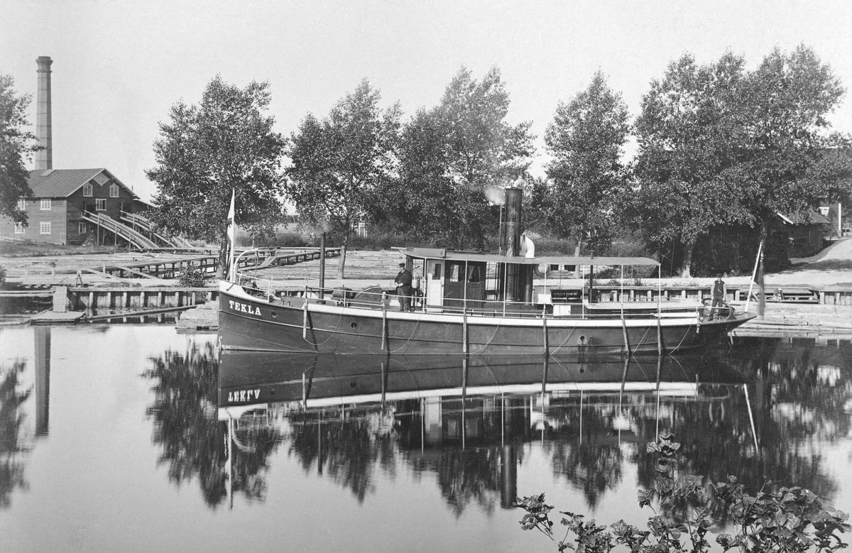 Motiv från Linköpings hamnområde 1892. Vid kaj ses bogserångfartyget Tekla, byggd i Stockholm 1889 för trafik på Kinda kanal. Fartyget tillhörde P. Wikström i Stockholm som även ägde Linköpings ångsåg vars anläggning ses till vänster.