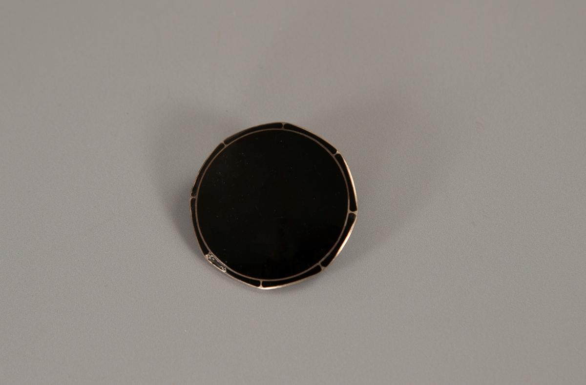 Sirkelrund med antydet åttekantform, glatt og dekket av sort emalje på fremsiden.