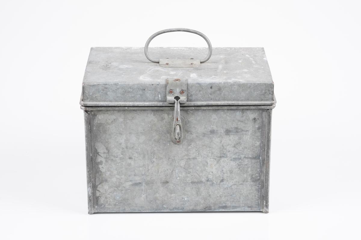 Oppbevaringsboks av blikk. Lokket lukkes med hengsler som kan låses med hengelås. På lokket det er håndtak.