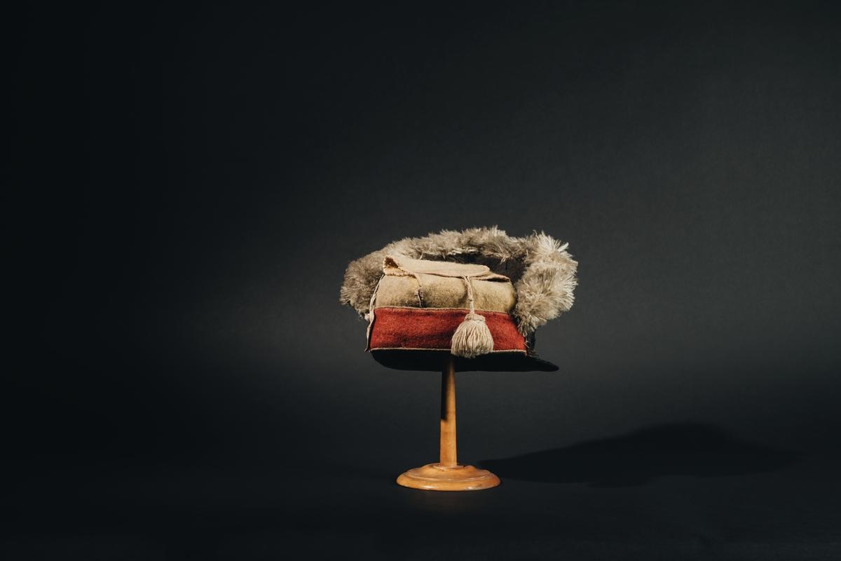 Grenadiermössa, rysk, kantad med björnskinn och försedd med kejsarinnan Katarina II:s namnchiffer. Material: svart filt med kantning av snörmakeri upptill, gula flikar med tofs vid sidorna samt framtill läderskärm med namplåt av koppar.