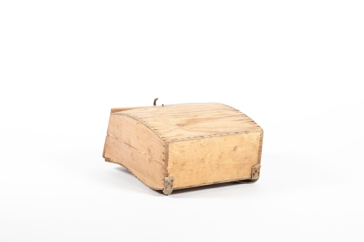 """Sekkens bakplate i finér og er bøyd slik at den passer til ryggens form (utsvinget ved korsryggen). Også forsiden av finér, mens sideplatene er treplanker, og det samme gjelder bunn og lokk. De ulike stykkene er spikret sammen, men lokket er skrudd fast til bakplaten ved hjelp av henglser festet til en list på innsiden. På lokket er det skrudd fast en lærrem, som kan tres på en spiker på forsiden. På baksiden er bæreselene festet til en ring, som henger i et påskrudd kobberbeslag. Selene er laget av et grovt tekstilstoff, og øverst er de """"klinket"""" fast i en lærrem v.h.a. sinknagler med jernringer. Under er selene skrudd fast i bunnen. Rundt lærremmen på selene er det bundet fast en taustump i naturmateriale."""