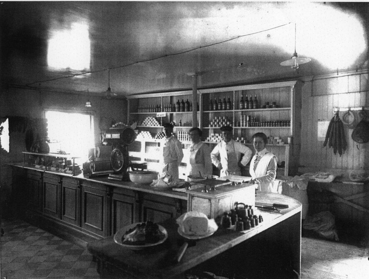 Handelsbod med fyra personal bakom disken. Charkuterier. En köttkvarn står på den bortre disken. Korvar hänger på väggen. Lanthandel