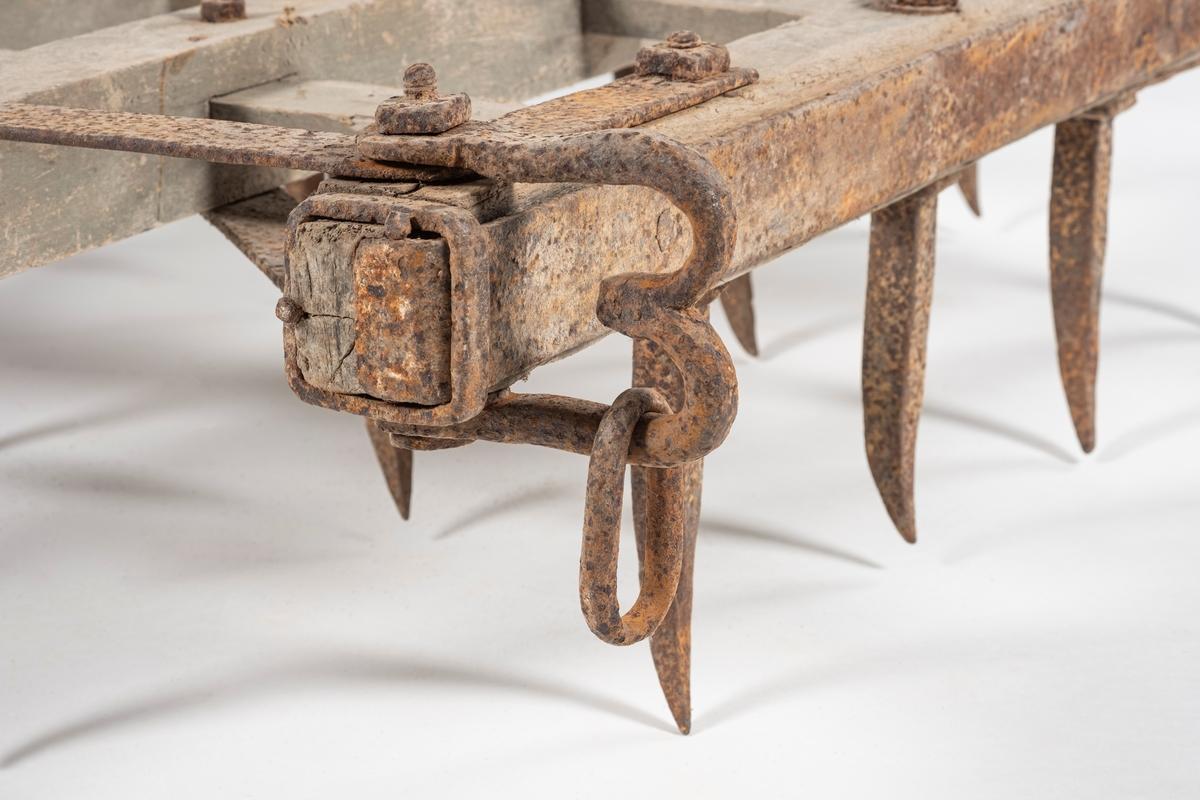 Kroktindharv av jern og tre. Treramme med påmonterte kroktinder og styrearm. Harven har 20 svakt krummede tinder skrudd fast til rammen. Det er to avstivere av jern mellom styrearmen og rammen. Rundt styrearmen er det festet en skinnrem, muligens et belte. I forkant av harven er det et jernbeslag med drått - eller trekkhempe.