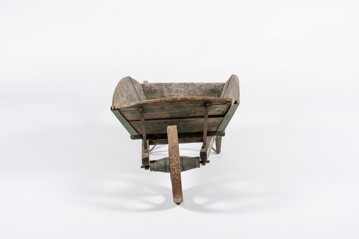 Trillebår i tre. Selve båren består av fire skråstilte, avrundede vegger utformet av horisontale planker. Bunnen er fire planker i samme retning som langsideveggene. Håndtak som går langs bunnen av båren og fremover mot hjulets aksling, som er festet med jernbeslag. Hjulet er av tre og har seks eker, forsterket med jernbånd.