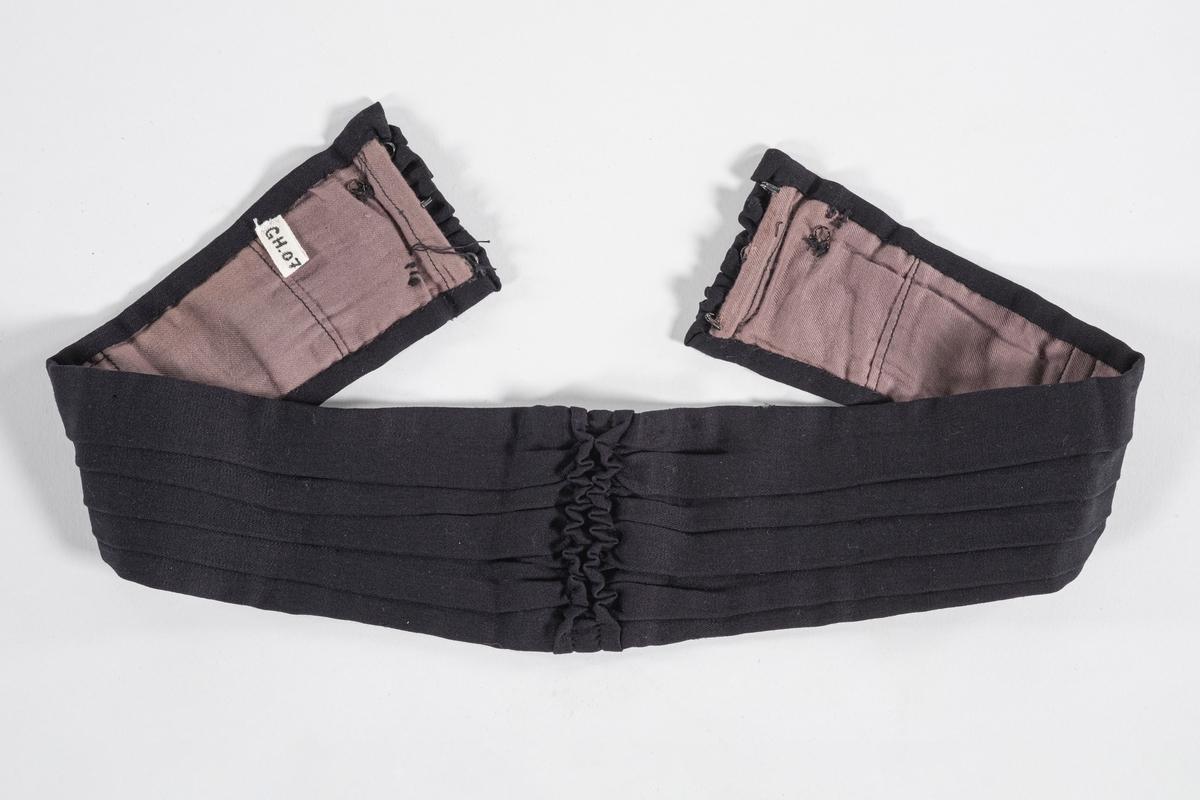 Belte i svart bomull med fôring i lilla bomull. Det er folder langs beltet med rysjer i midten og ved hektepartiet. Beltet hektes sammen med metallhektere. Det er sydd inn 7 spiler i beltet.