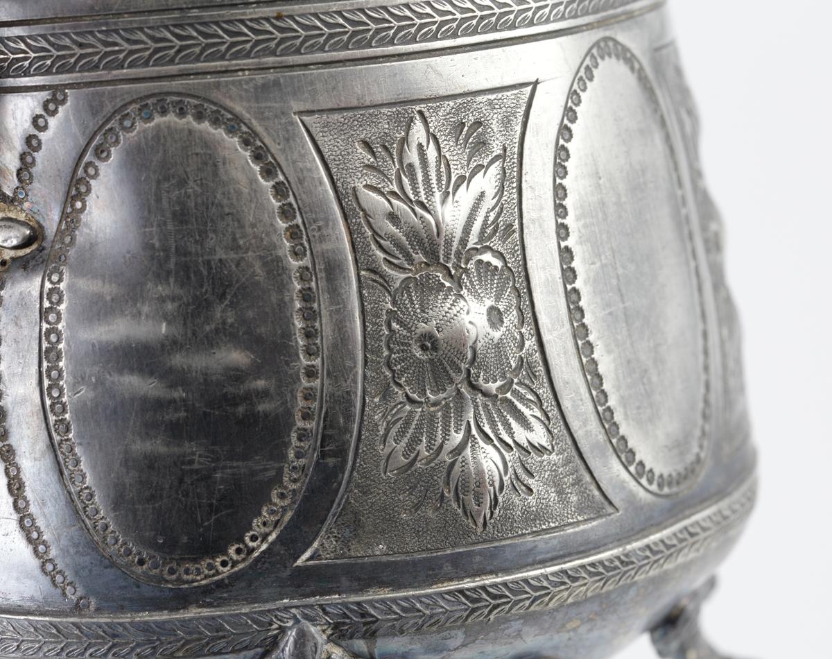 """Kaffekanna av tenn. Päronformad modell, med dekorerat liv. Högt, svängt handtag merd bladansatser. Pipen är lång och svängd samt försedd med benring och kannelyrer vid basen . De fyra fötterna är gjutna i bladform. Kupigt lock, med svarvad lockknopp av mässing.  Under kannans botten är instämplat """"1417"""", i övrigt saknas stämplar."""