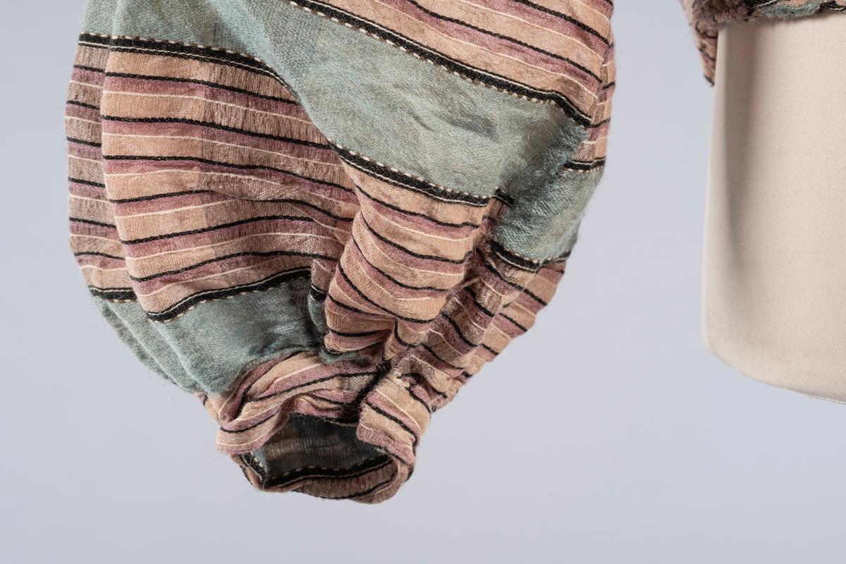 Grønt og beige jakkeliv til dame, med fem spiler av plast - tre i ryggen og to i hver side. Jakkelivet lukkes med hemper og hekter i front. Foret med bomull- eller linlerret. Armhulen er foret med tynnere bomullstoff, selve ermet er uforet. Puffskuldre og ballongermer. To hemper og to tøyhekter i ermelinningene. Folder i nedre kant av ryggen som ender i en spiss bak. Grønne felt med smale beige og brune striper.
