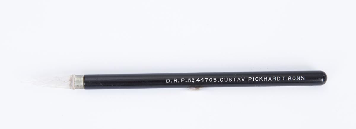 """Pren, hulleredskap til broderi, i plast eller glass og tre. Lakkert sort skaft i tre med sølvskrift: """"D.R.P.No 41705. GUSTAV PICKHARDT. BONN"""". Tupp i glass el plast med langs gående riller."""