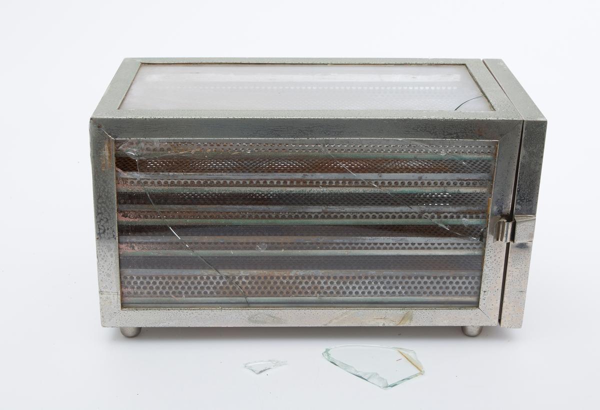 Avlang kassse med glassvegger og metallramme. Fem skuffer satt in overhverandre laget av gjennomhullet metall. Nederst et tettt brett til å legge tabletter av formalin brukt til sterilisering. Glassdør på kortveggen. Noe errodert/rustent, ellers hel