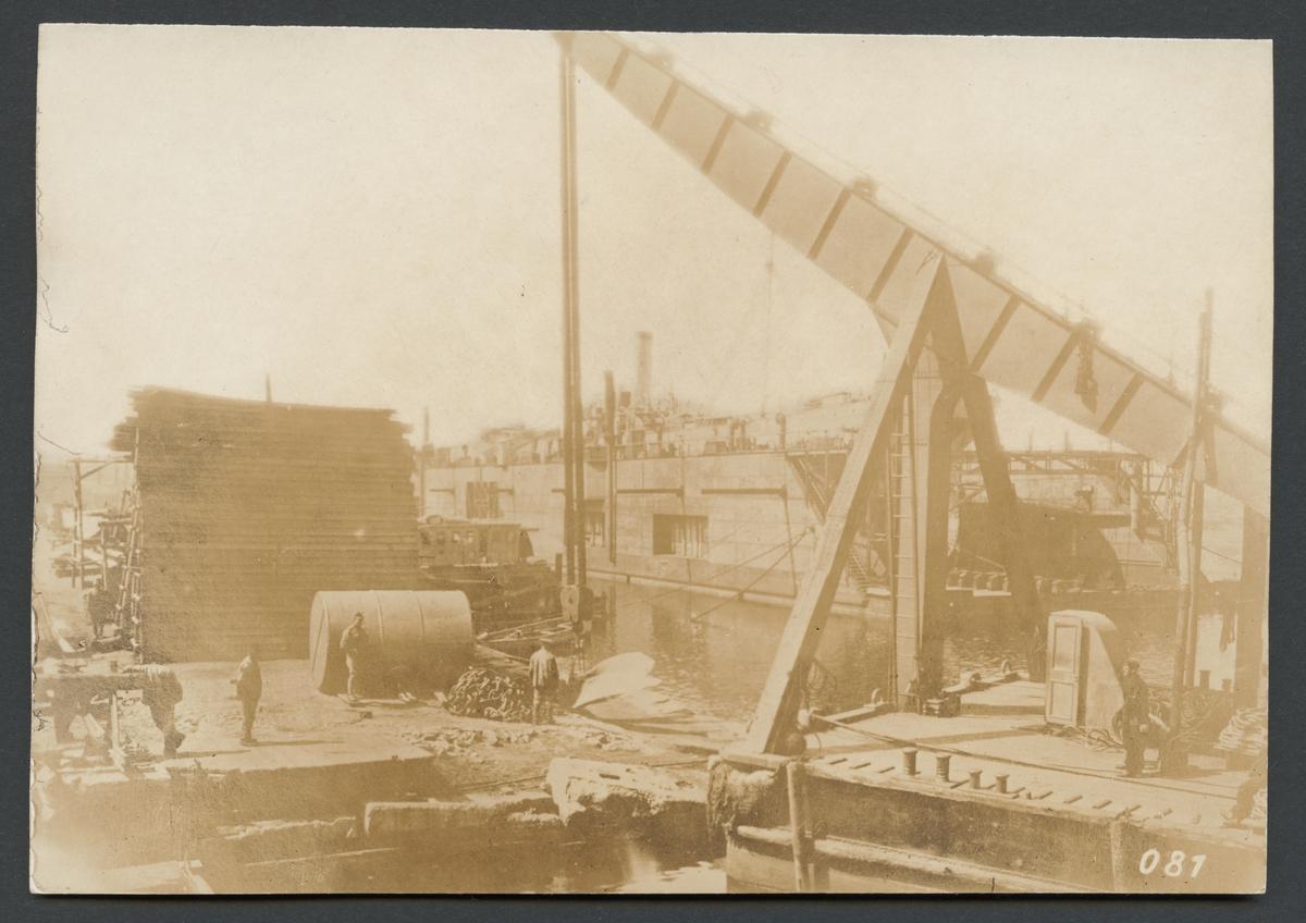 Bilden visar hamnarbetare på en kaj i Odessas hamn. Förgrunden dominera av en lyftkran och bakgrunden syns en flyttdocka.  Originaltext: