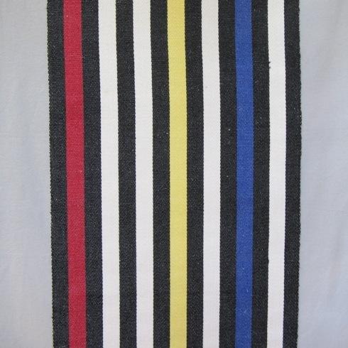 Långrandig löpare i hellinne i kraftig kvalitet, vävd i kypert med inslagseffekt på rätsidan. Varpen består av tvåtrådigt lingarn i svart, halvblekt, blått, gult, rött. Inslaget består av halvblekt lintowgarn. Fållarna är tråcklade.  Alla ränder är lika breda. Varannan rand är svart och varannan är antingen blekt eller färgad. Det börjar med svart i ytterkanten och sedan vit, blå, vit, gul, två vita och sist en röd mellan resterande svarta. Det finns en färgställning där de svarta ränderna bytts ut mot grå och i kanterna är det en rosa rand och en blå rand och i mitten en turkos rand.  Löparen med modellnamn Per är formgiven av Ann-Mari Nilsson och tillverkad av Länshemslöjden Skaraborg. Den finns med  på sidan 34-35 i vävboken Inredningsvävar av Ann-Mari Nilsson i samarbete med Länshemslöjden Skaraborg från 1987, ICA Bokförlag. Se även inv.nr. 0001-0012,0014-0040.