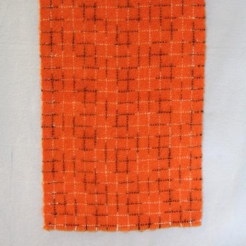 Halsduk vävd i tuskaft av ullgarn. Varpen och inslaget är enfärgat orange med rutor i flamfärgat garn i svart och vitt. halsduken har 10 mm lång frans och är lätt beredd.  Halsduken är formgiven av Ann-Mari Nilsson. Se även inv.nr.0112-0114 Halsduk samt inv.nr.0115 Vävprov i andra färgställningar.