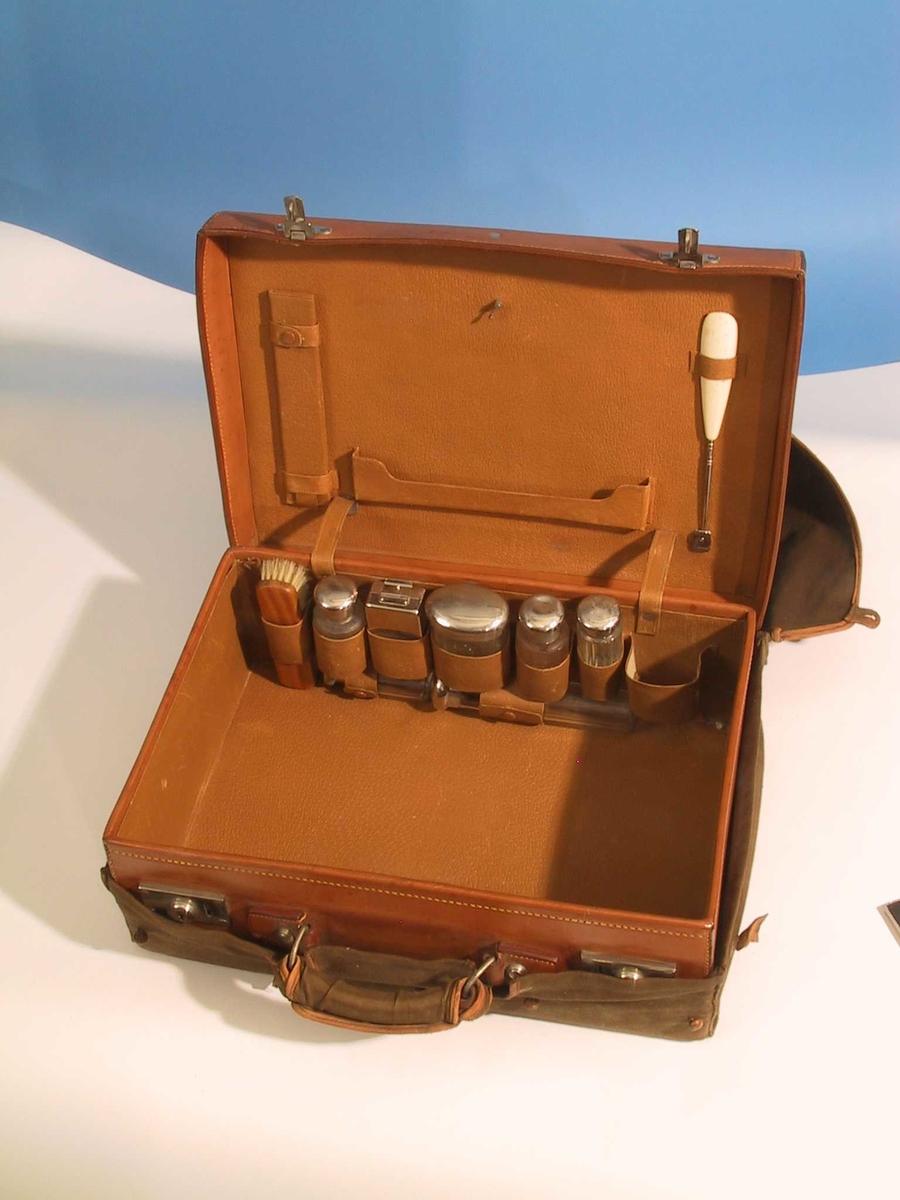 Kuffert m. bærehandtak og varetrekk. Hemper og lommer innvendig. Inneholder 8 løse deler i tillegg til kufferten og dens beskyttelsestrekk. Dette er klesbørste, skohorn, såpekopp og diverse glass med lokk, alt passer i hemper og lommer inne i kufferten. En av flaskene inneholder væske.