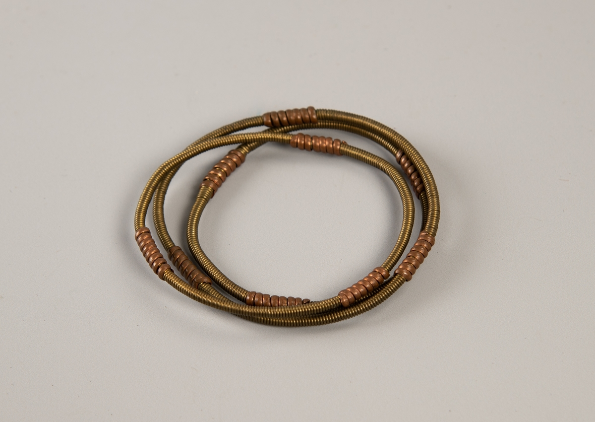 Tre armbånd fra Afrika, tatt med hjem av en norsk kaptein. Armbåndene er i messing og kobbertråd.  Tre tynne armbånd omviklet med tynn messingtråd, på tre steder  omviklet med litt tykkere kobbertråd ca. 1,5 cm hvert stykke.
