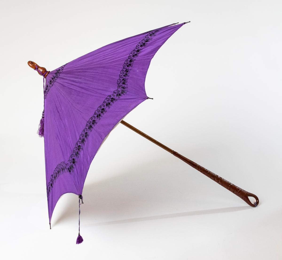 Parasoll av lila siden, ett mönster är invävt i tyget, foder av vitt siden. Handtaget av trä är snidat.