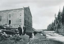 To menn står foran en industribygning i teglstein. I bakgrun