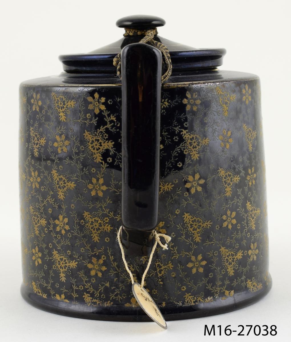 Tekanna, svart med tryckt småmönstrad dekor i brons/guld på de vertikala sidorna.