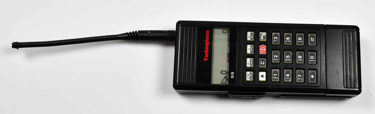 """Anmärkningar: Mobiltelefon med tillhörande fodral och batteriuppladdare.Telefonen i svart hårdplast med gummiklädd sändare.Märke """"Technophone"""",Type : PC 117,Serial No 30722.Tillverkad i England av Technophone LTD.På framsidan 20 knappar : siffrorna 0-9, * och Verkstad, fabrik: PC 117 Serial No 30722"""