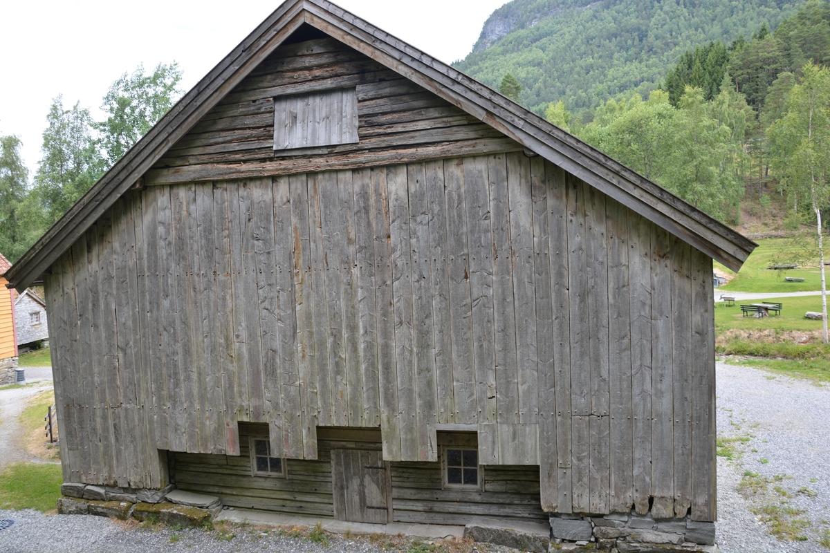 Grindbygg i to etasjar. Takpanner. Dobbel dør på begge langsider, i første og andre (låvebro) etasje.