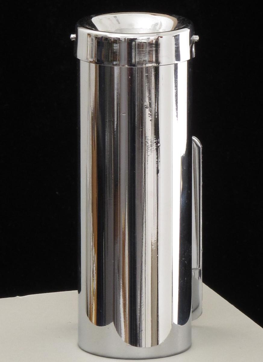 Sylinderformet askebeger, med beslag beregnet for montasje på vegg. Av rustfritt stål. 2 stk. den ene er i originalemballasje, den andre uten. Begge er ubrukte. Firmastempel under bunnen, og påtrykt emballasjen.