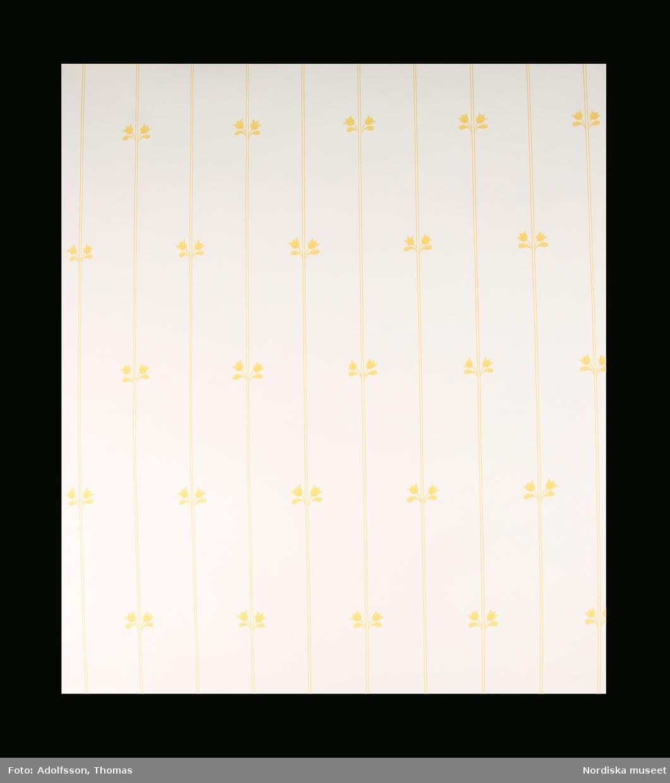 Tapetrulle, del av. Vit bottenfärg med smala lodräta linjer i gult på fem centimeters avstånd från varandra. På varannan rand horisontalt två tulpaner som böjer sig utåt från linjen och flankerar den. Tulpanerna i raden ovanför och under placerade ett steg åt sidan horisontalt, i s.k. half drop. /Maria Maxén 2015-04-07
