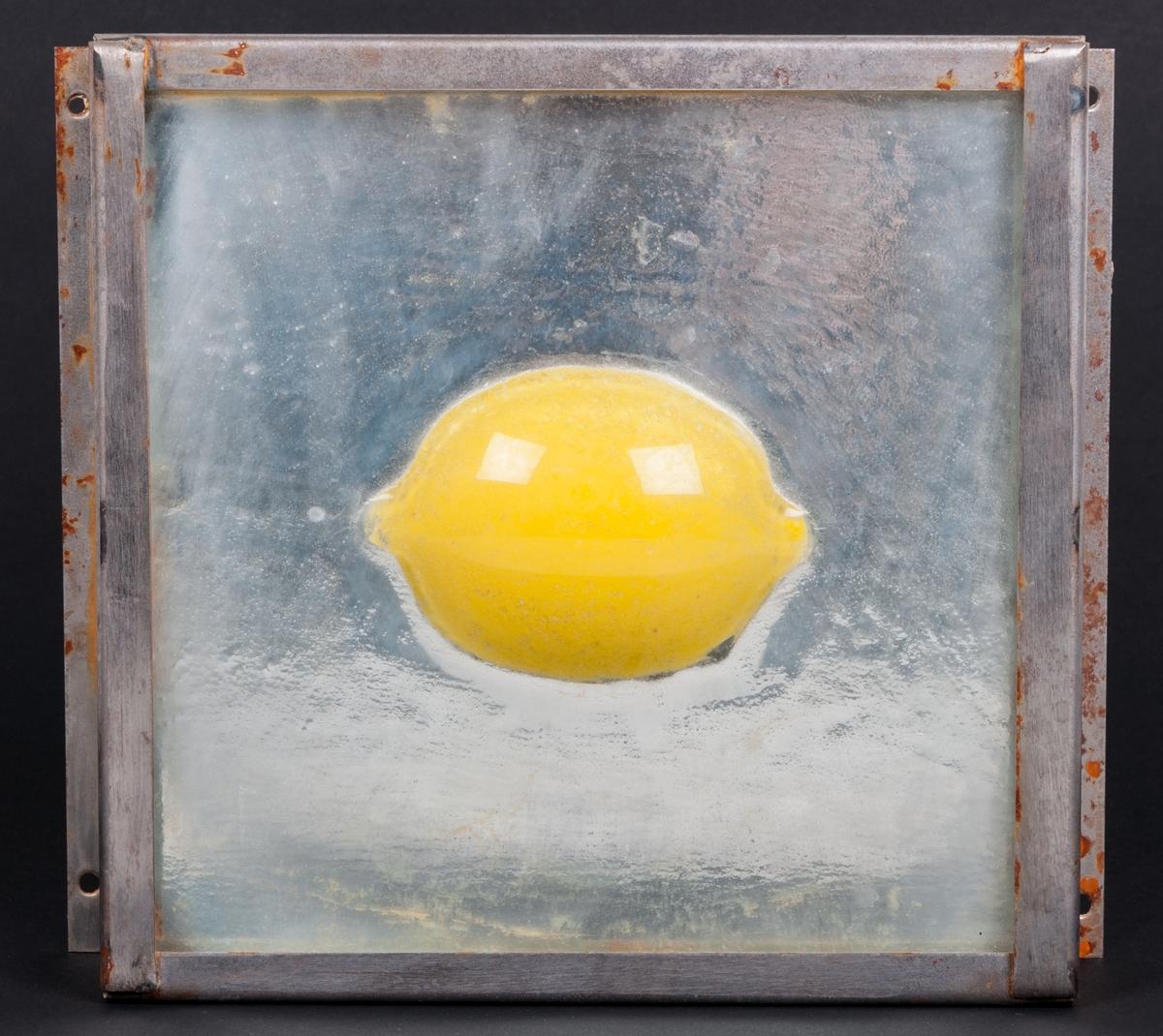 """Objekt, skulptur, i glas och stål, """"Spegelbild"""" (alt. Gul citron) av Lena Forslund-van Leer. Kvadratisk, något strukturerad, klar glasskiva med gul citron i relief i centrum. Bakom glasskivan är ett spegelglas. Glasskivorna infattade i obehandlad stålram."""