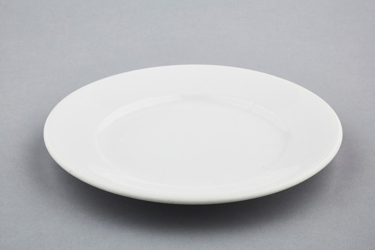 En hvit tallerken i steintøy merket med Porsgrunn Porsenlen på bunnen.  Serviset ble brukt på Skallum gård på Stabekk i Bærum under 2. verdenskrig.