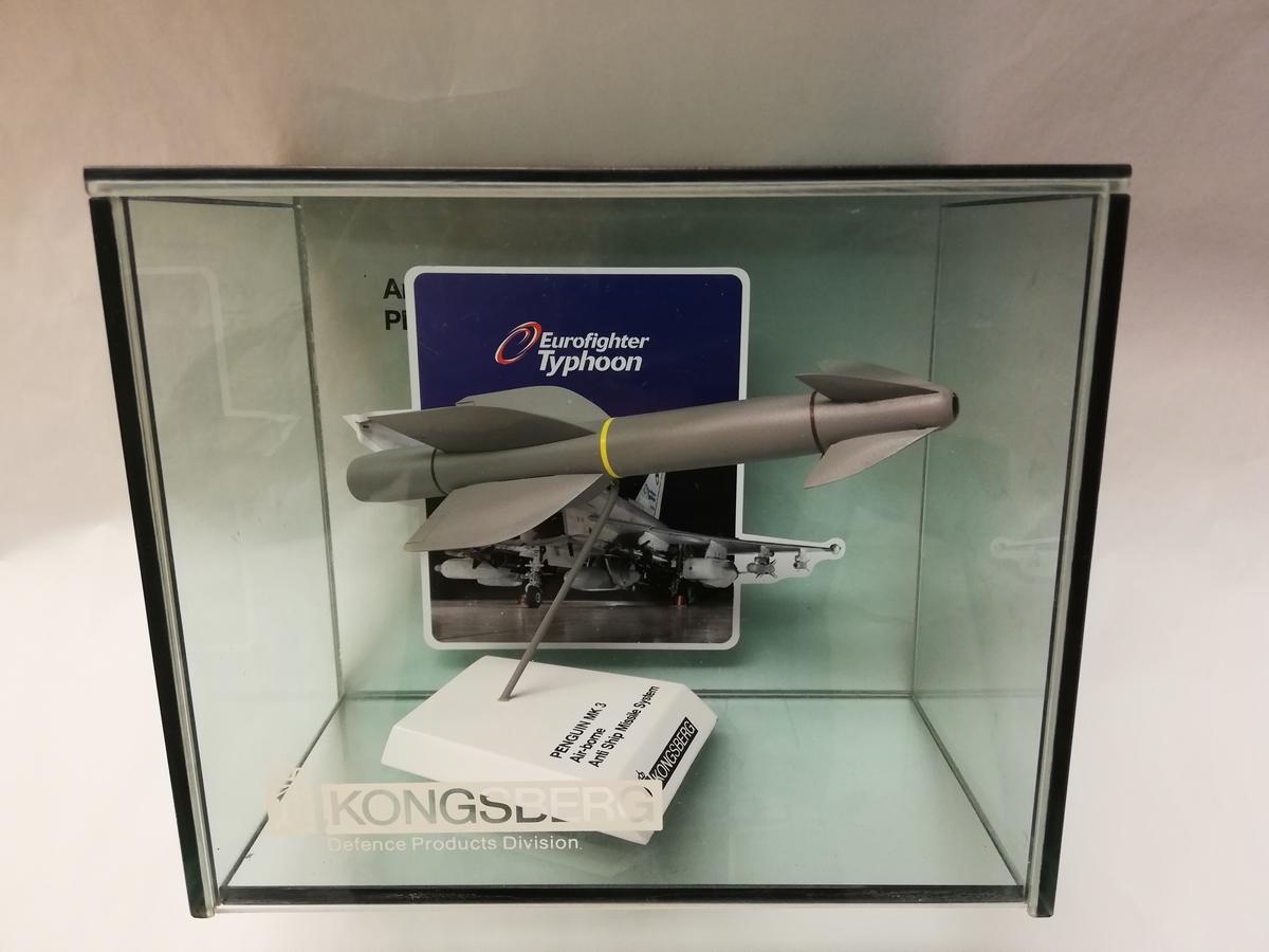 Modell av Penguin MK 3 Airborne Anti Ship Missile System. Modellen er plassert i monter med bilde av Eurofighter Typhoon i bakgrunn.