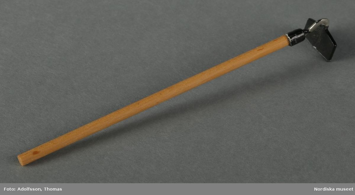 6 st trädgårdsredskap av metall med långa handtag av trä: a) en högaffel, b) en räfsa, c-d) 2 spadar med röda detaljer på skaftet, e) en grön spade samt f) en hacka för ogräsbekämpning. Redskapen står lutade mot dockskåpets yttervägg intill trädgården i dockskåpet NM.0331721+.