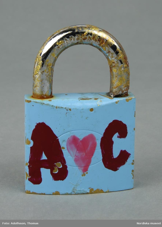 Ett fyrkantigt avknipsat blåmålat kärlekslås av metall, med initialer påmålade med vinröd färg samt rosa hjärtan, på båda sidor. /Lena Kättström Höök 2019-01-23