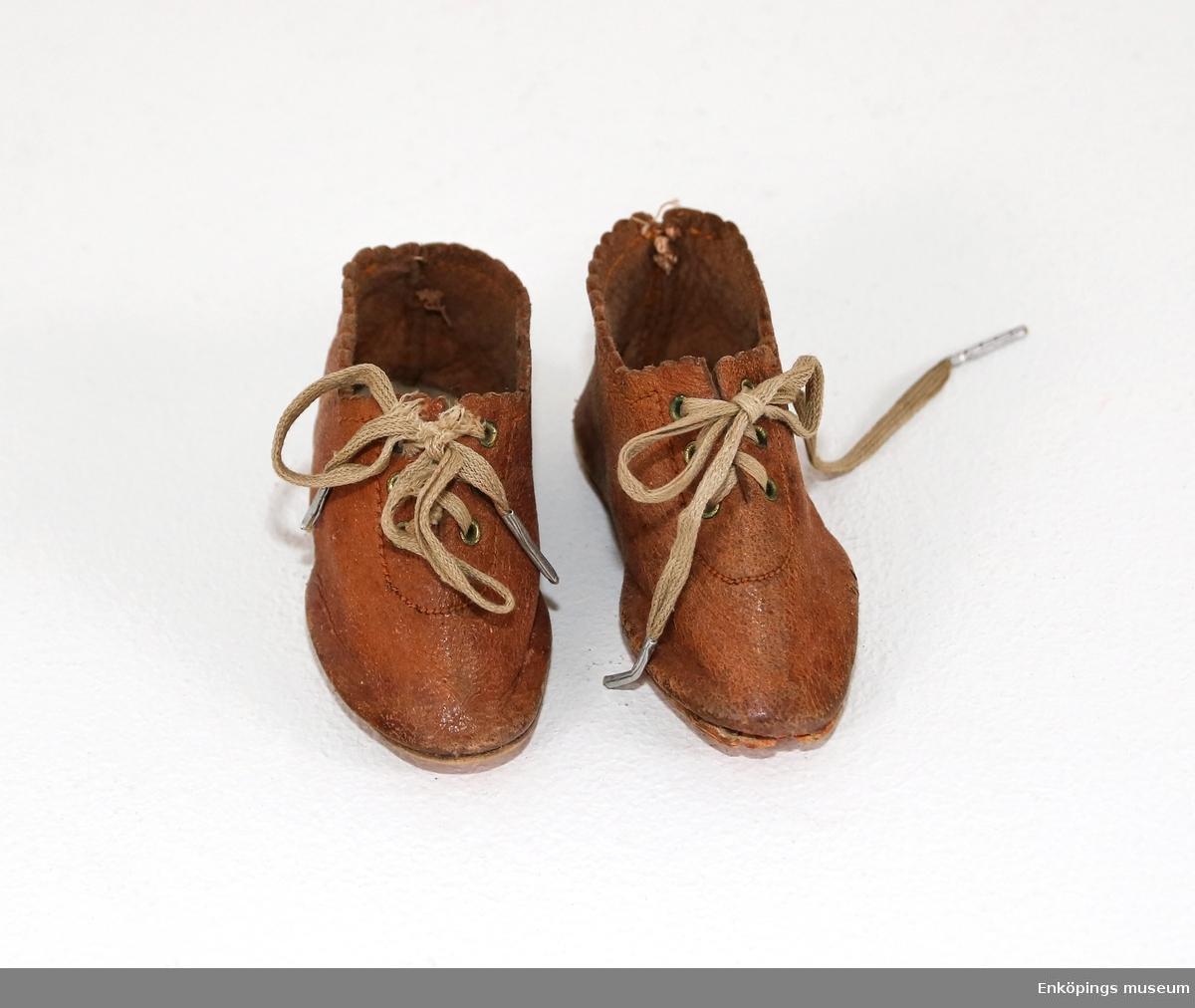 Docksko av läder med knytning.