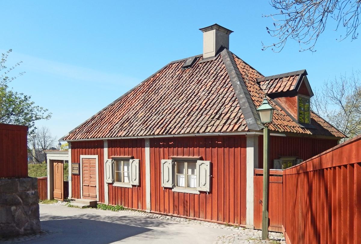 Sparbanken i stadskvarteren på Skansen är en timrad envånig byggnad klädd med stående locklistpanel. Fasaden är målad med röd slamfärg, snickerier i grå linoljefärg. Taket är högt, valmat och toppigt, klätt med enkupigt lertegel.   Byggnaden är troligen uppförd omkring 1700. Huset flyttades från Bondegatan 54 på Södermalm i Stockholm och återuppfördes på Skansen på sin plats i stadskvarteren 1946.