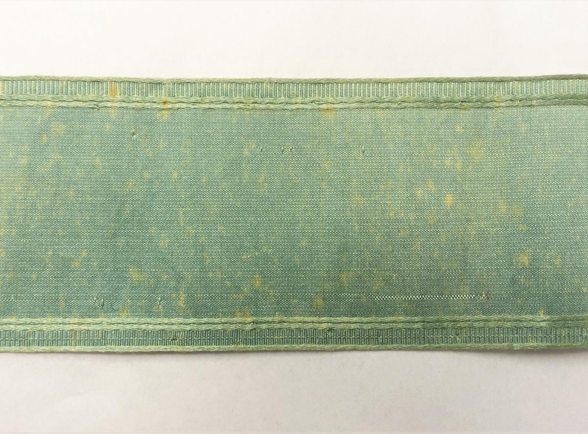 Grønn tekstilbånd. Endene på båndet er klipt.