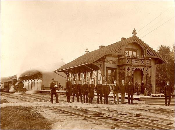 Jernbanepersonalet foran Hønefoss stasjon. I bakgrunnen damplokomotiv type XV med blandet tog