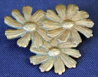 Platt kopparstycke format till tre stycken prästkragsliknande blommor som går in i varandra och tillsammans bildar en triangelliknande form. På broschens baksida sitter en nål med säkerhetsnålsfunktion, med vilken man fäster fast broschen på hatten.