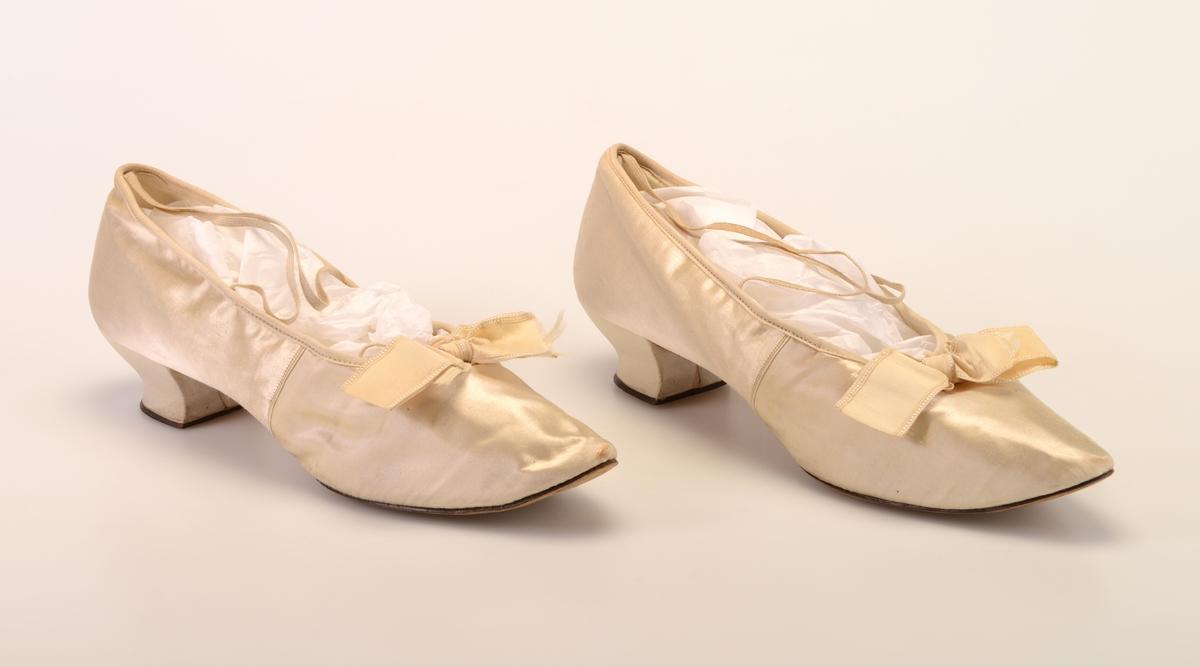 Et par damesko av hvit/elfenbensfarget silke. Foran er tåen er spiss. På tåen/i utringningen er det festet en ecrufarget silkesløyfe. Skoene er foret med hvitt linstoff i den fremre delen, mens den er foret med hvitt skinn i den bakre delen. Innersålen er av hvitt skinn. I hælkappen er det festet to strikk som krysses foran. Dette er for at skoen skal sitte bedre på. Undersålen er av brunt lær. Skoene har snellehæl som er trukket med hvit silke og har såle av brunt lær. Skoene skal ha vært brukt som bryllupssko i 1897.