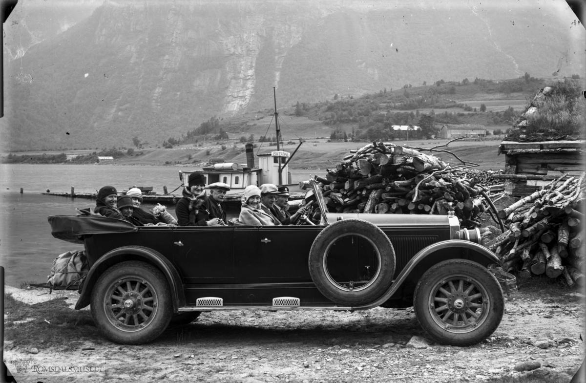 Buick 1926-modell 7-seter med en ekstra person i forsetet..Bak bilen ser vi kaia og båten D/S Eikesdal som trafikkerte Eikesdalsvatnet i mange tiår fram til begynnelsen av 1960-tallet. Da ble transporten lagt om. Båten ble erstattet av ferge som gikk på vatnet i 25-30 år. I neste fase ble det bygd vei langs vatnet og fergaruta ble nedlagt.