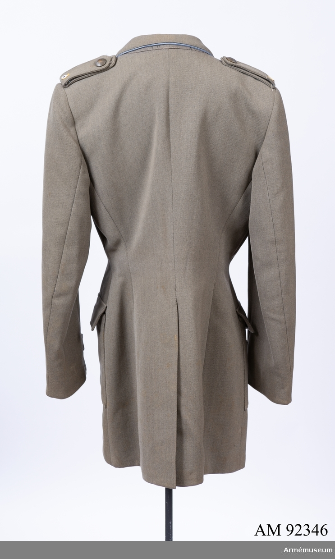 Jacka sydd i grå yllediagonal med märken och knappar för Svenska Blå Stjärnan. Kring kragen en blå passpoal. Nedersta knappen saknas.