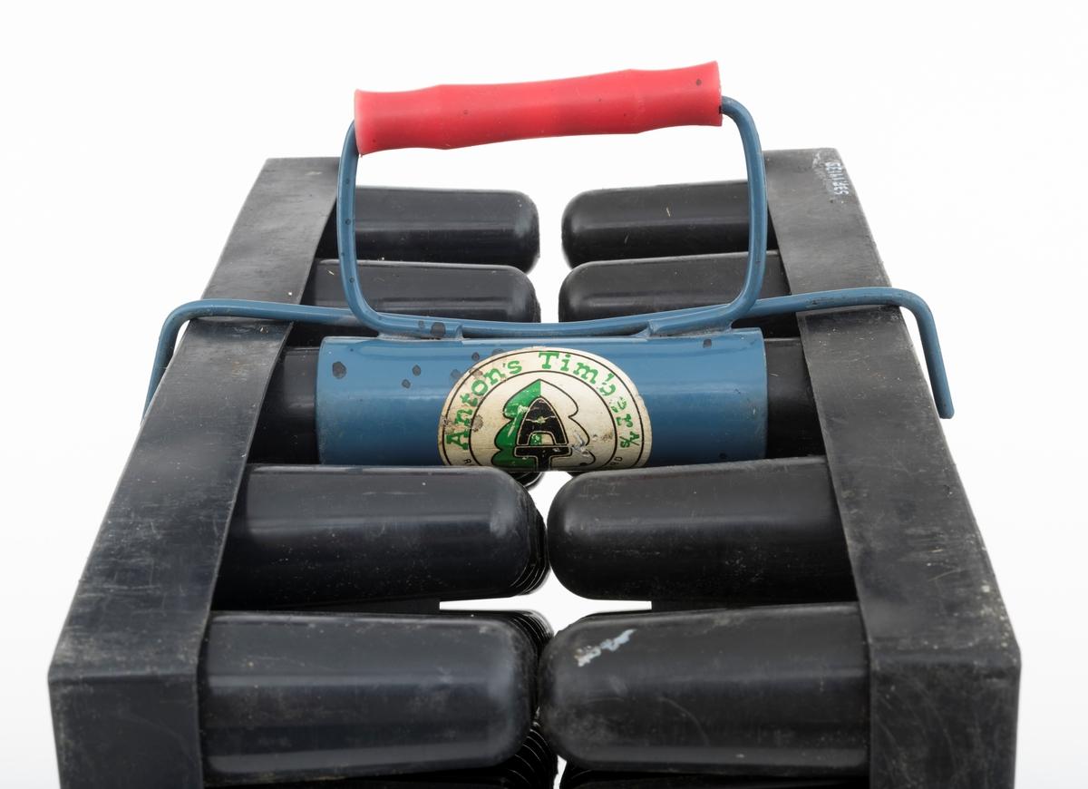 """Bærehank - handtak - for to plastkassetter med hylser for produksjon av såkalte pottebrettplanter eller pluggrotplanter. Denne bærehanken er bygd opp omkring et 10,5 centimeter langt jernrør som er litt konkavt, altså litt videre i ytterendene enn på midten. På yttersida av dette røret er det påsveiset ei handtaksbøyle og ei """"låsebøyle"""", lagd av 4 millimeter tjukk ståltråd. Handtaksbøyla er påtredd en rød plastholk med cirka 1,5 centimeters utvendig diameter. Denne komponenten reduserte belastningen på fingrene under løftig og bæring. Denne komponenten skulle plantøren gripe rundt hver gang plantebrettet skulle løftes eller flyttes. Handtaket ble montert ved å stille pottebrettene på høykant, underside mot underside (altså med de overjordiske delene av plantene utovervendt). Deretter tredde man de ytterste pottene på midtrekkene inn i planterøret, presset brettene mot hverandre, og vred på handtaket, slik at låsdebøylenes ytterkanter omsluttet ytterkantene på brettene. Bærehandtaket er blålakkert. Det er påklistrert et sirkelrundt merke fra leverandøren. Sentralt i dette merket er det ei strektegning av et stilisert grantre, overskrevet med bokstavene """"AT"""", som er intialene til Olav Antonsens firma Anton's Timber AS. Fullt firmanavn og adresse er plassert på en ring som omslutter det nevnte sentralmotivet.  Pottebrettene var rektangulære (39,8 X 29,9 centimeter i overkant) og snaut 8,4 centimeter høye. På undersida var det 9 rekker med plastpotter, 10 eller 11 enheter i annenhver rekke - til sammen 95 enheter - som er avstivet i forhold til hverandre ved hjelp av diagonale plastribber på undersida. Pottehullene har en diameter på 2,9 centimeter i overendene, men smalner noe nedover. I botnene er det dreneringshull med 1,1 centimeters diameter. De tidligste pottebrettene var slette innvendig. Etter at det viste seg at mange av pottebrettene utviklet deformerte røtter - såkalt """"rotsnurr"""" - støpte man pottebrett med innvendige vertikale riller som skulle lede planterøt"""