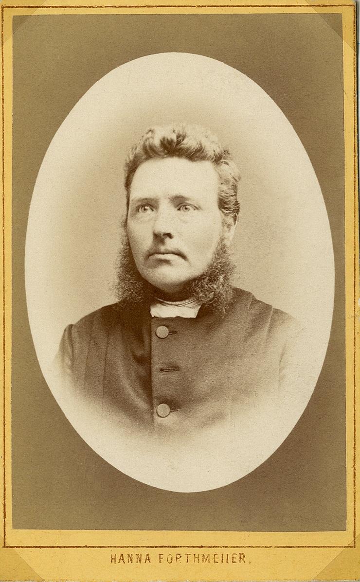 Porträttfoto av en man med polisonger, klädd i prästrock med prästkrage.  Bröstbild, halvprofil. Ateljéfoto.