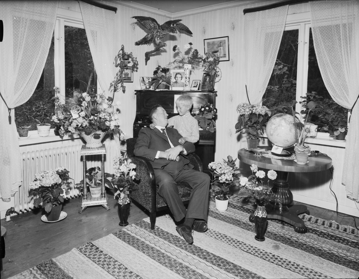 Man och pojke i hemmiljö omgivna av blommor, Östhammar, Uppland