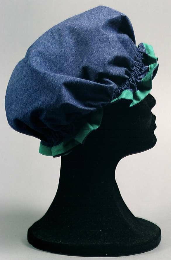 Tillverkade av mörkblå bomullslärft kantade med gröna snedslåar. Förkläde med fickor fram och öppning bak. Stängs med en knapp i nacken. Mössa i puffad form med resår runt om.